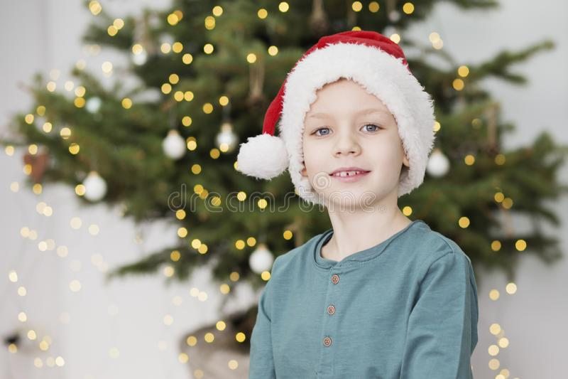 Little Boy in de Hoed van de Kerstman Portret van mooi jong geitje in Kerstmiskleding voor een verfraaide Kerstmisboom royalty-vrije stock afbeeldingen