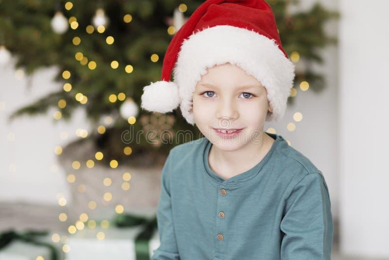 Little Boy in de Hoed van de Kerstman Portret van mooi jong geitje in Kerstmiskleding voor een verfraaide Kerstmisboom stock fotografie
