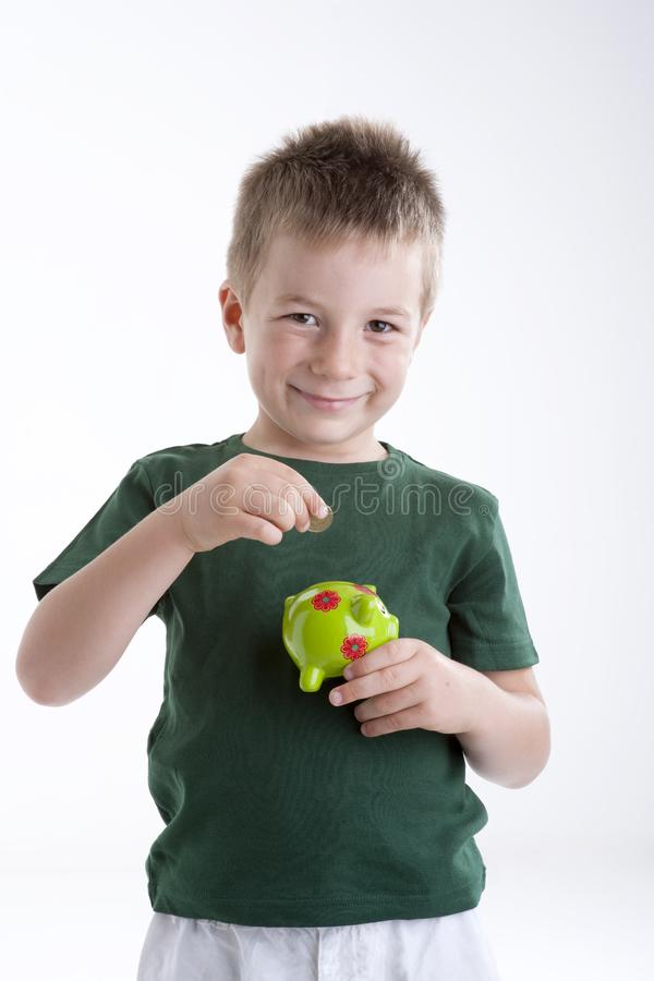 Download Little Boy Depositing Money In His Piggy Bank. Stock Photo - Image of blond, piggy: 15409622