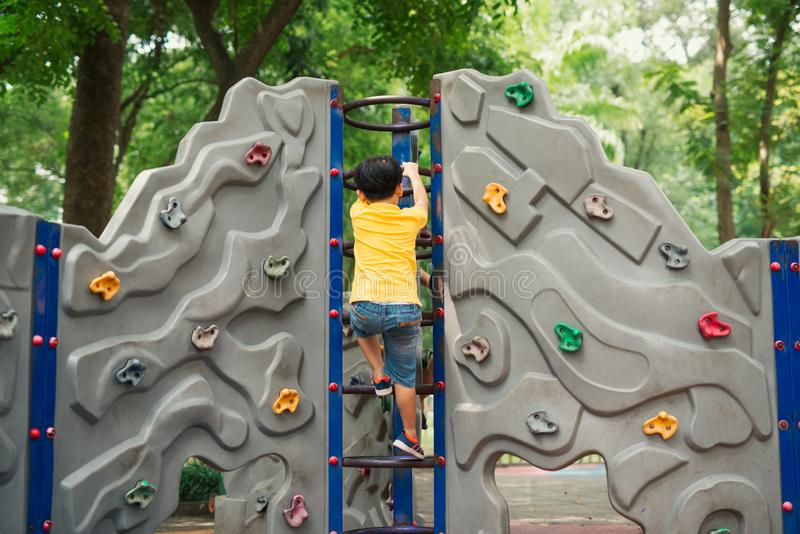 Little Boy die ladder op speelplaats beklimmen stock foto's