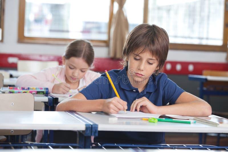 Little Boy die Nota's met binnen Klasgenoot schrijven royalty-vrije stock afbeeldingen