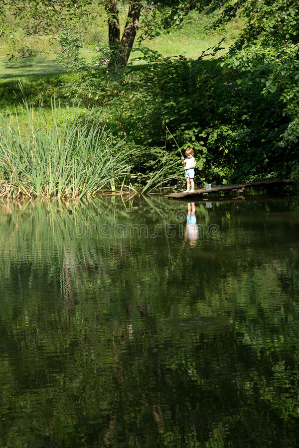 Little Boy die van de Rand van Houten Dok vissen stock fotografie