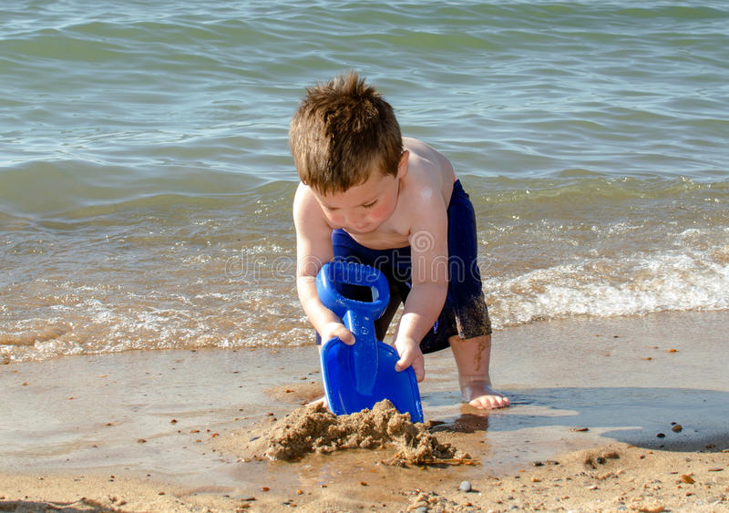 Little boy digging sand on the beach royalty free stock photo