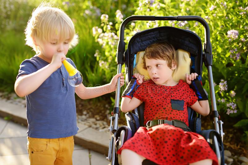 Little boy and a disabled girl playing together in the summer park. Child cerebral palsy. Family with disabled kid stock image