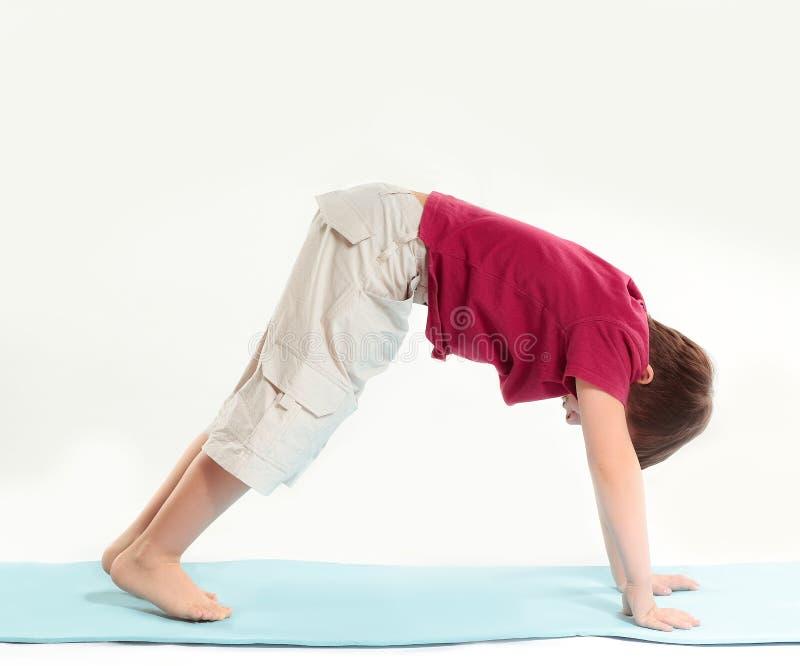 Little boy does health-improving gymnastics.isolated on white background.  royalty free stock photo