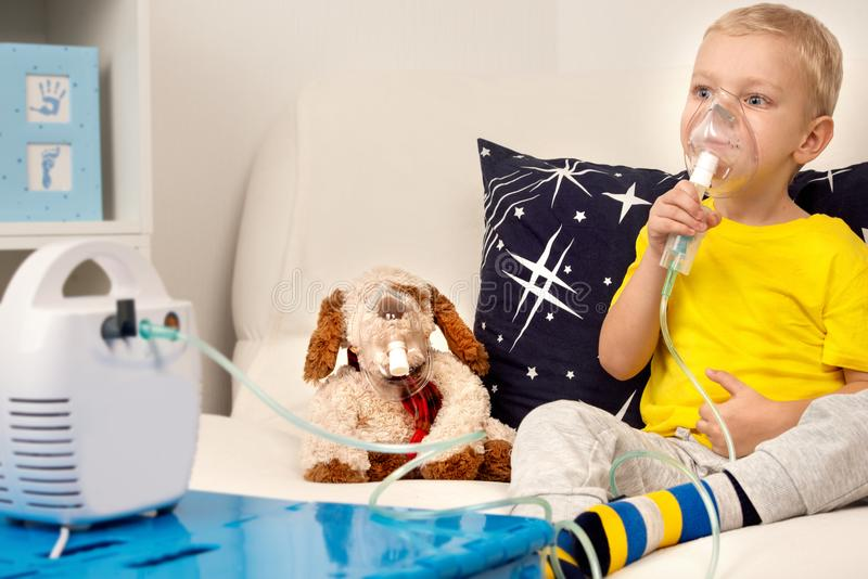 A little boy does inhalation with a nebulizer. A home treatment. A child and a toy dog in masks royalty free stock photo