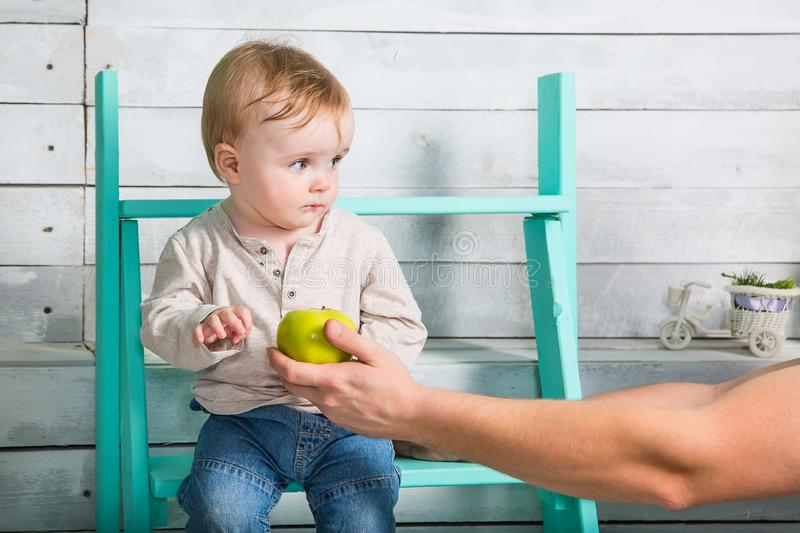 A little boy does not want to take an apple from a stranger. He looks incredulous and sits on the steps indoor. White wooden. Background stock photography
