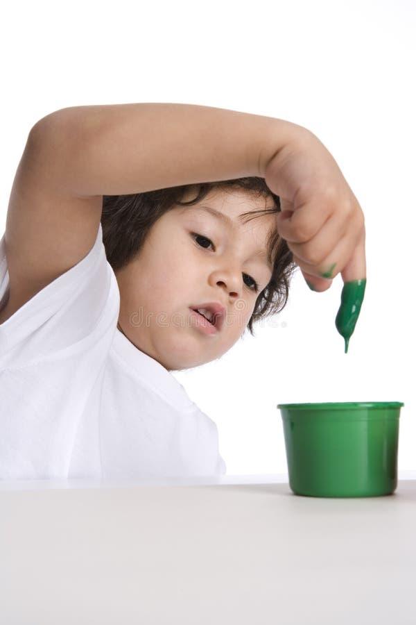 Little Boy dompelt Zijn Vinger in Groene Verf onder royalty-vrije stock foto