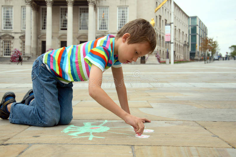 Little Boy Drawing With Chalks On Pavement Stock Image