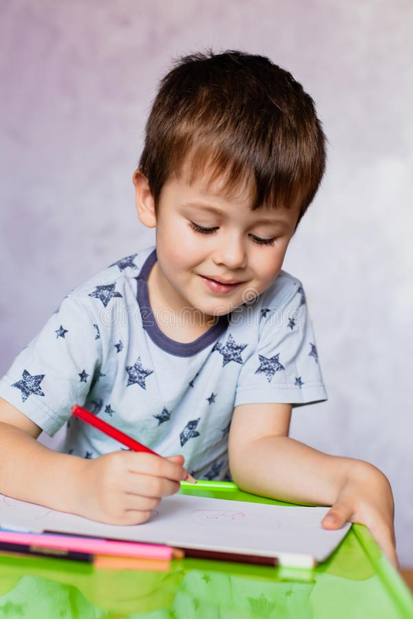 Little boy drawing with color pencils. Boy, drawing a picture for fathers day. Small boy draws at the table. Little boy drawing with color pencils. Little boy is royalty free stock images