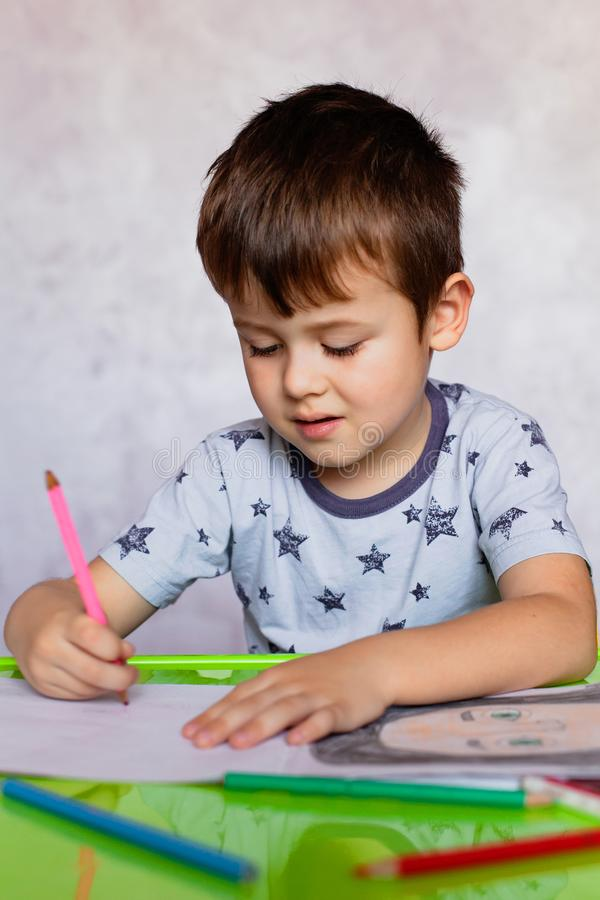 Little boy drawing with color pencils. Boy, drawing a picture for fathers day. Small boy draws at the table. Little boy drawing with color pencils. Little boy is stock image