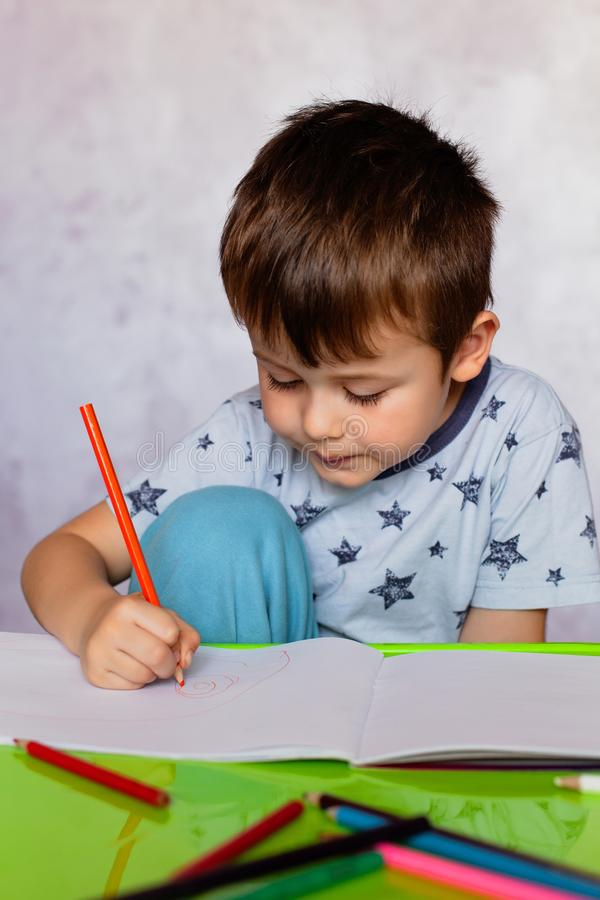 Little boy drawing with color pencils. Boy, drawing a picture for fathers day. Small boy draws at the table. Little boy drawing with color pencils. Little boy is royalty free stock photography
