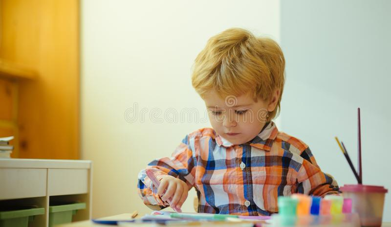 Little boy on drawing lesson. Serious kid enjoy painting with brush and colours wearing colourful shirt. Young child royalty free stock image