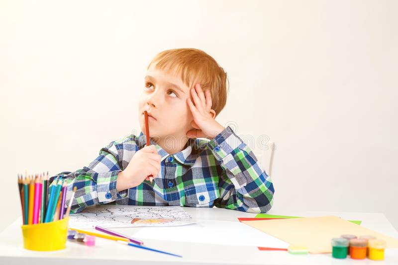 Little boy drawing picture in art class. Kid thinking about new creative idea. Cute preschool child drawing at home. Education, stock images