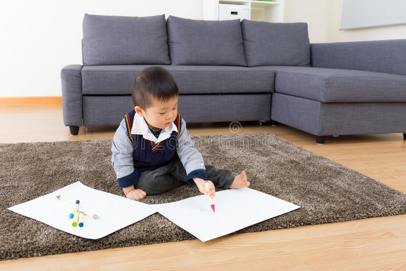 Little boy drawing picture and seating on carpet stock images