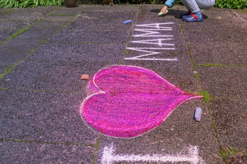 Little boy drawing of pink heart with chalk on sidewalk royalty free stock photos
