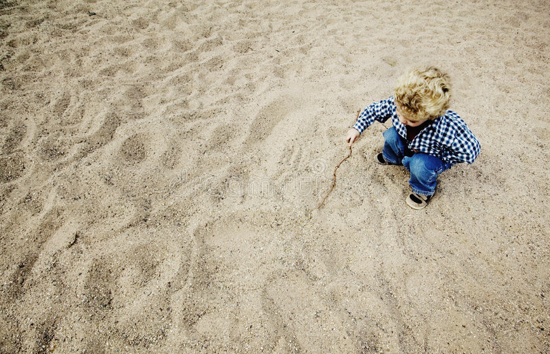 Little Boy Drawing in the Sand royalty free stock photos