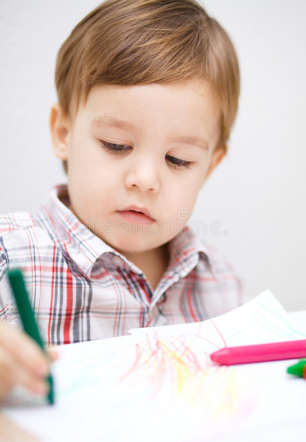 Little boy is drawing on white paper stock image