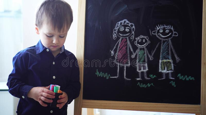 Little boy draws family on black board. royalty free stock images