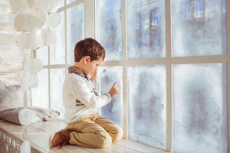 Little boy draws on a frozen window in the winter royalty free stock photo