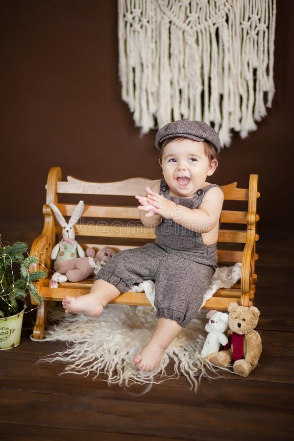 Little boy dressed as a bully, a yard boy with a cap, sits on a bench royalty free stock image