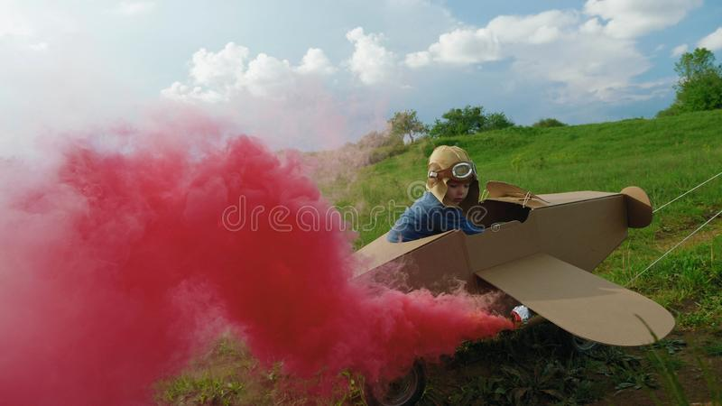 Father and son playing with cardboard airplane at the daytime. Little boy dressed in a cap and glasses aviator, flying in a cardboard airplane with attached royalty free stock photos
