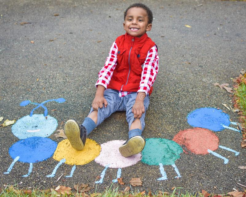 Little Boy Pulling Up Pants. A little boy, dressed in a red vest and blue jeans, sitting by chalk ark, pulling up the legs of his pants royalty free stock photo