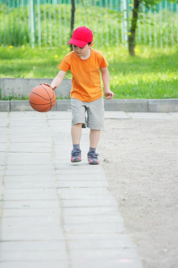 Little boy dribbling basketball. Little boy in orange shirt dribbling basketball outdoors royalty free stock images