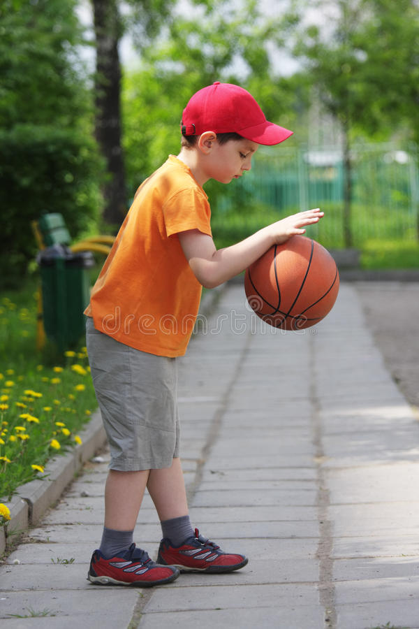 Little boy dribbling basketball sideview. Little boy in orange dribbling basketball outdoors sideview royalty free stock photo