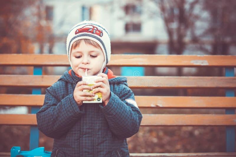 Little boy drinking. Autumn portrait little boy thinks and drinking juice a tube stock photos