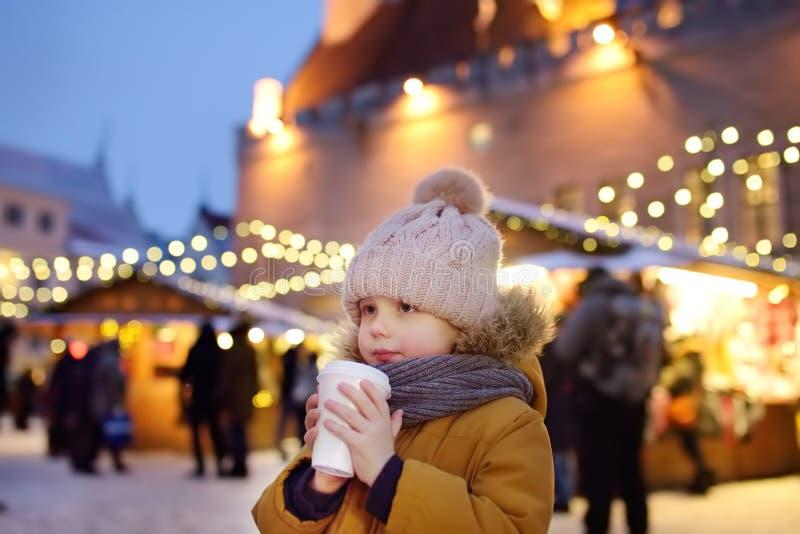 Little boy is drinking hot chocolate or child mulled wine on Christmas market in Tallinn, Estonia stock image