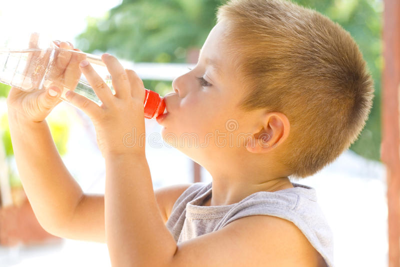 Little boy drinking water. Summertime royalty free stock photo