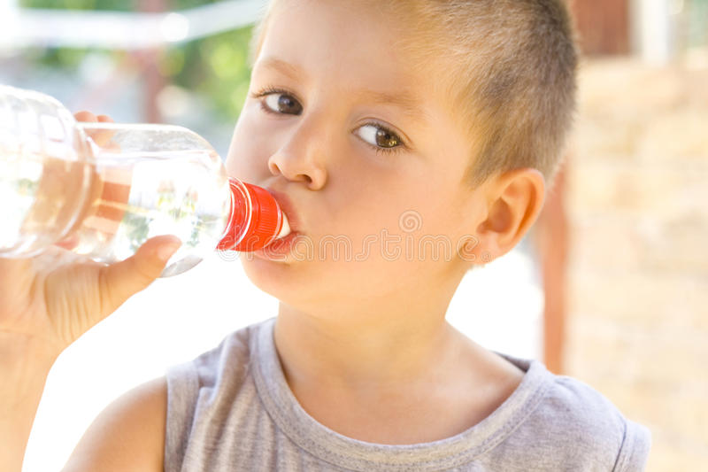 Little boy drinking water. Cheerful kids stock photography