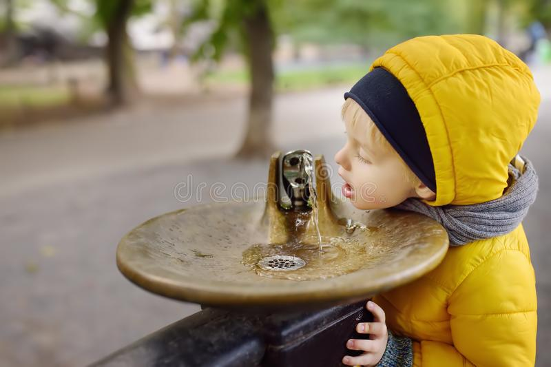 Little boy drinking water from city fountain during walking in Central Park, Manhattan, New York, USA stock photos