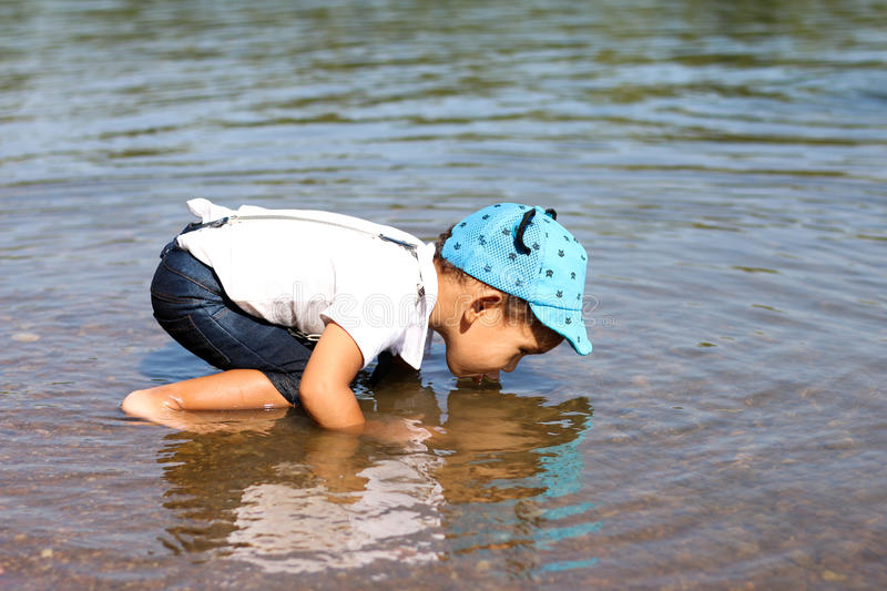 Little boy drinking water from the river.  stock photography