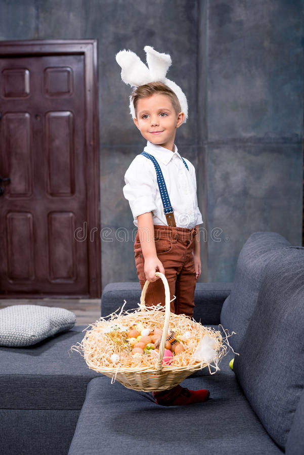 Little boy with Easter eggs. Cute little boy in bunny ears standing on sofa and looking for Easter eggs royalty free stock photo