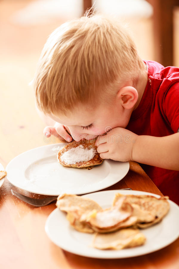 Little boy eating apple pancakes at home. Little funny boy eating with relish mael fried apple in pancake dough or apple fritters pancakes with icing sugar at stock images
