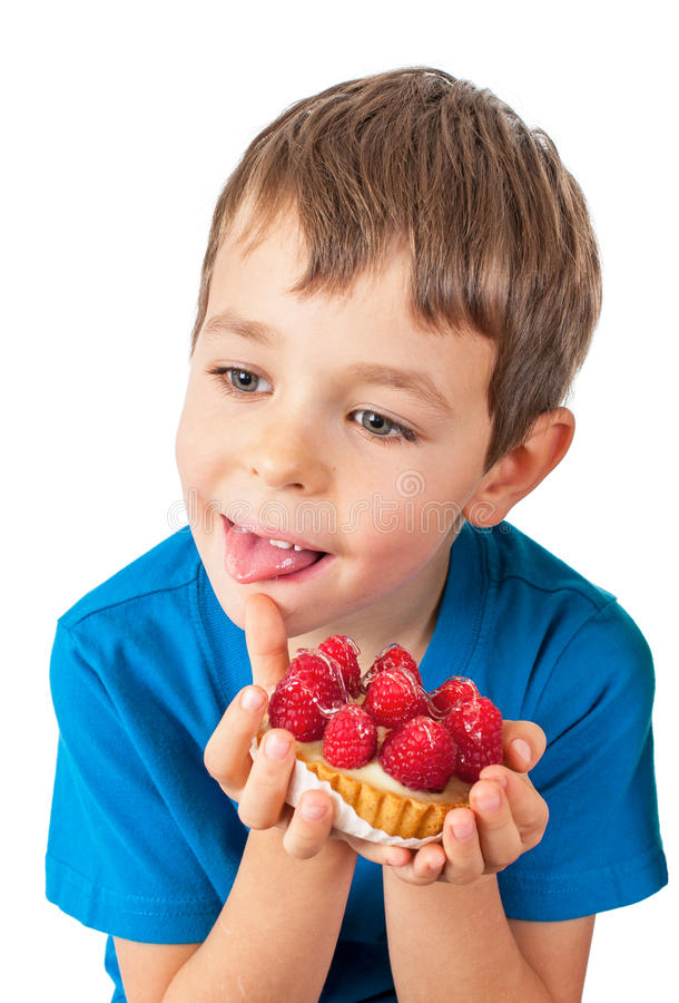 Little boy eating cakes. With fruits stock photos