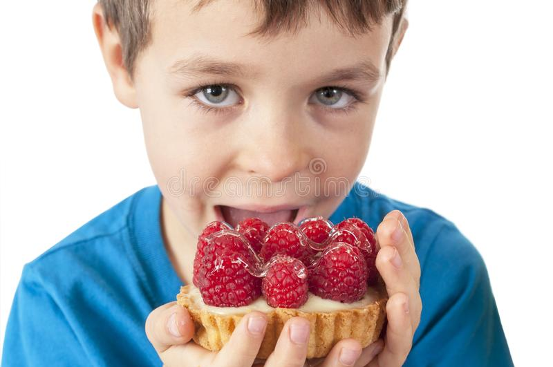 Little boy eating cakes with fruits royalty free stock image