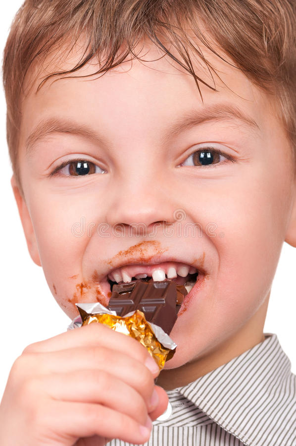 Little boy eating chocolate stock images