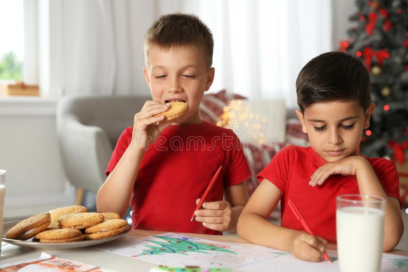 Little boy eating cookies while his friend drawing picture stock photos