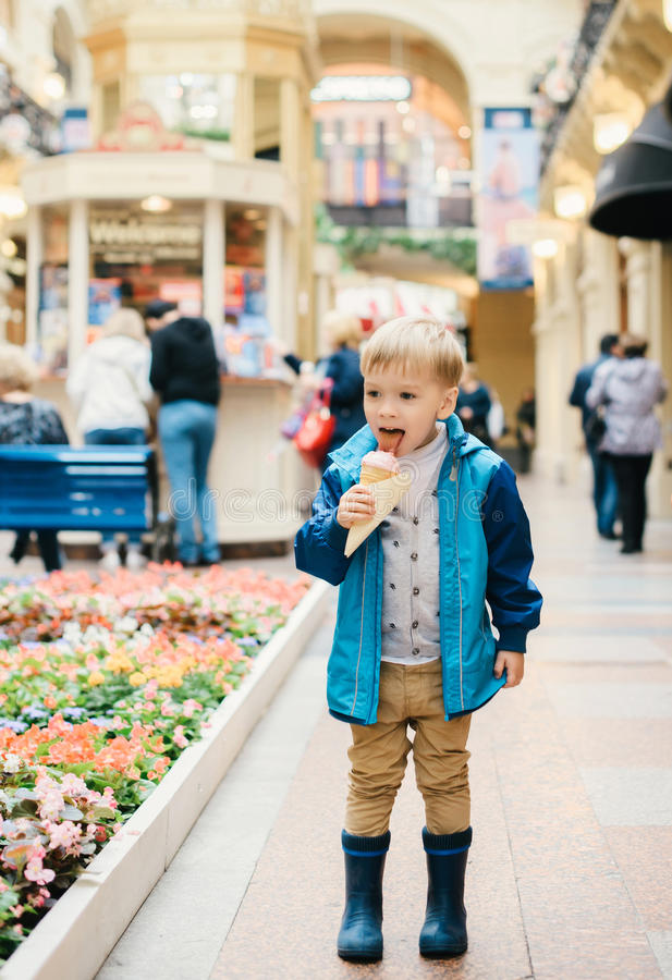 Little boy eating ice cream in a street royalty free stock photo