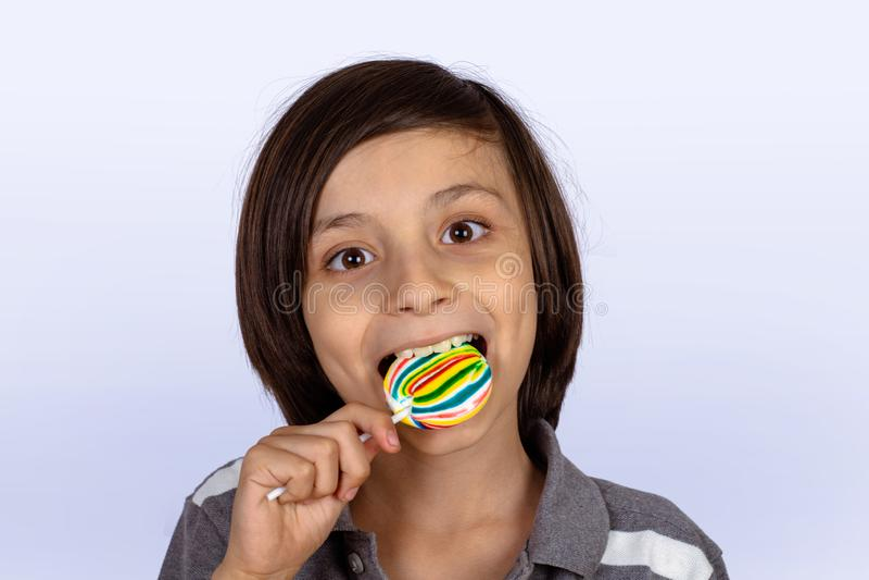 Little boy eating a lollipop stock photography