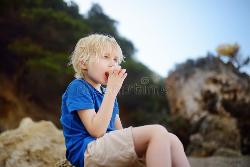 Little boy is eating peach during walking. Nature lover stock image