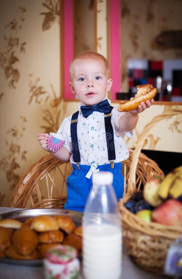 Little boy eating a pie in the kitchen. Shooting in the interior in retro style. Little boy eating a pie in the kitchen at the table. Shooting in the interior in royalty free stock images