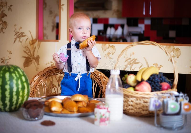 Little boy eating a pie in the kitchen. Shooting in the interior in retro style. Little boy eating a pie in the kitchen at the table. Shooting in the interior in royalty free stock photos
