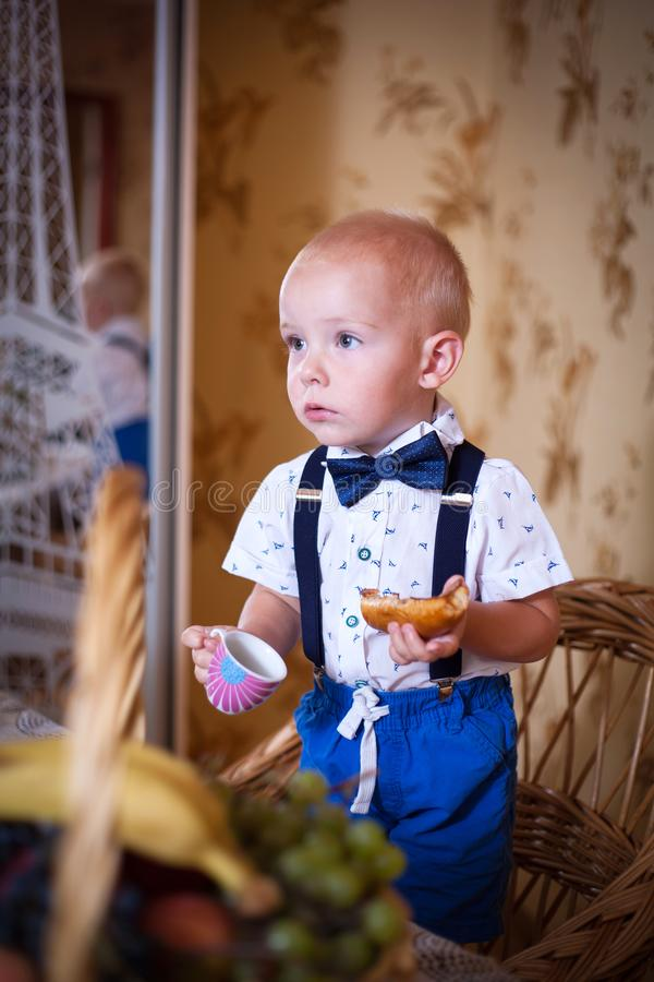 Little boy eating a pie in the kitchen. Shooting in the interior in retro style. Little boy eating a pie in the kitchen at the table. Shooting in the interior in stock photography
