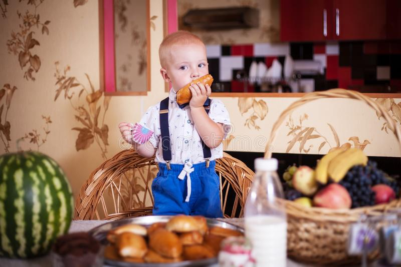 Little boy eating a pie in the kitchen. Shooting in the interior in retro style. Little boy eating a pie in the kitchen at the table. Shooting in the interior in royalty free stock image