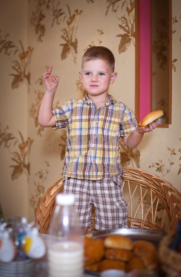 Little boy eating a pie in the kitchen. Little boy eating a pie in the kitchen at the table. Shooting in the interior in retro style royalty free stock image
