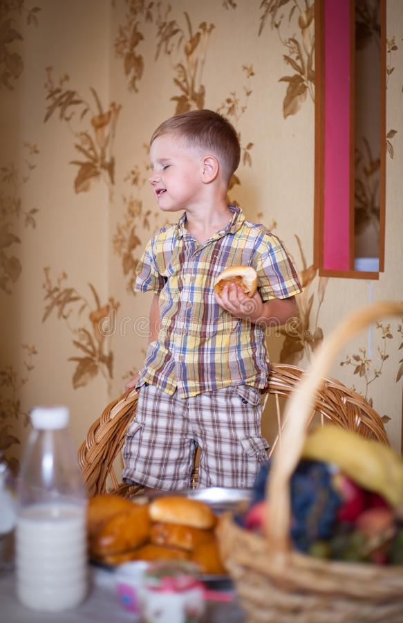Little boy eating a pie in the kitchen. Little boy eating a pie in the kitchen at the table. Shooting in the interior in retro style royalty free stock photos